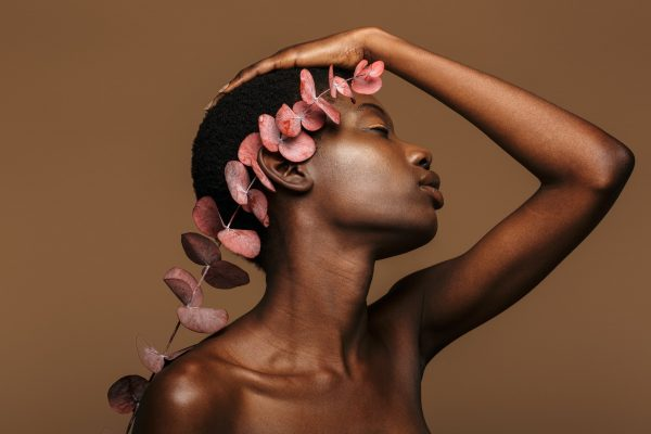 Beauty portrait of young half-naked african woman holding exotic flower