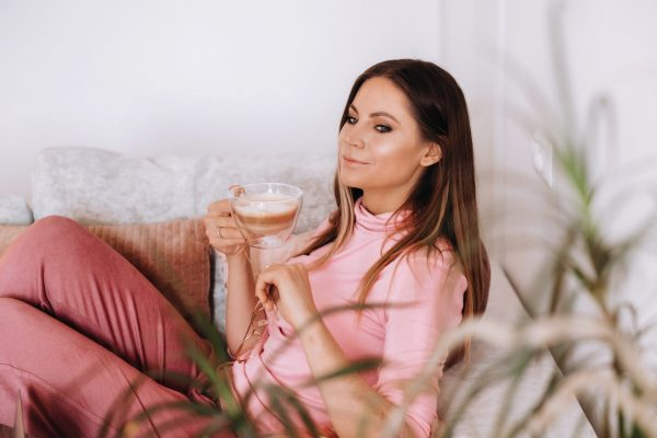 relaxed girl in the morning in pajamas at home drinking coffee .Inner peace.The girl is sitting comfortably on the sofa and drinking coffee dreaming about something.