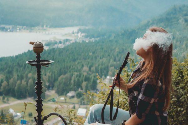 Women smoke hookah in a mountains