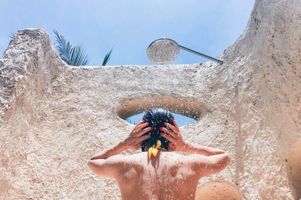 Young woman refreshing in shower near outdoor pool